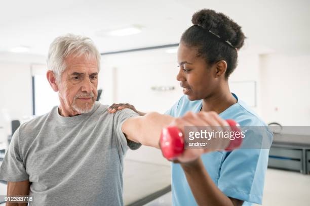 Physiotherapist correcting her senior patient with his shoulder posture as he lifts free weights