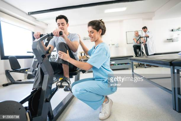 Physiotherapist correcting the posture of a patient on a static bicycle