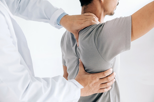 Physiotherapist doing healing treatment on man's back.Back pain patient, treatment, medical doctor, massage therapist.office syndrome 1161512437