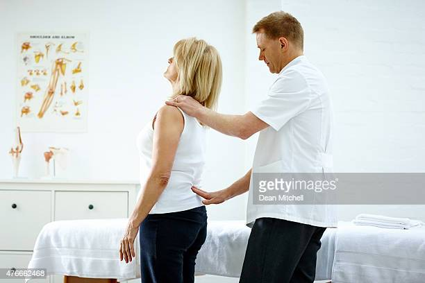 physiotherapist examining patient's lower back - lower back stock pictures, royalty-free photos & images