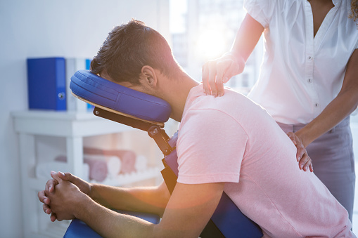 Physiotherapist giving back massage to a patient 636218646