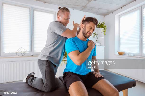 physiotherapist giving back massage to a sportsman - sports medicine stock pictures, royalty-free photos & images