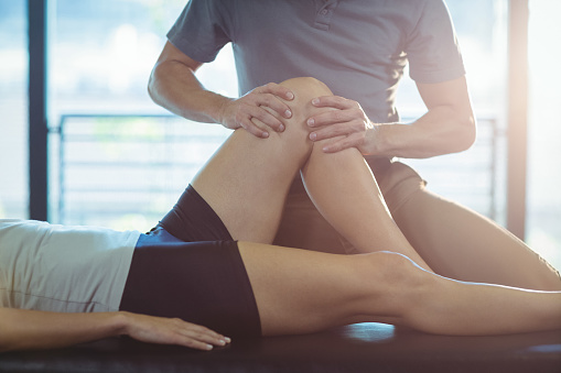 Physiotherapist giving knee therapy to a woman 613759168