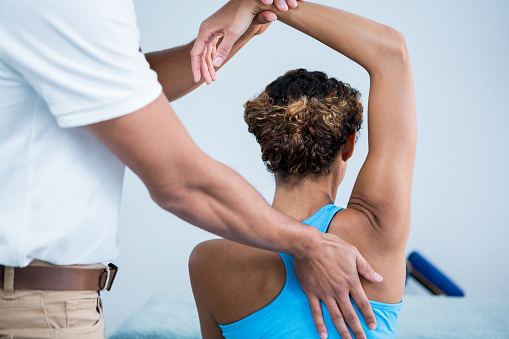 Physiotherapist giving shoulder therapy to a woman 636213780