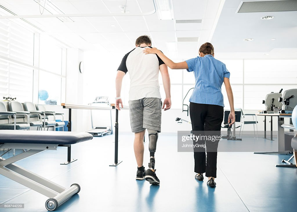 Physiotherapist helping young man with prosthetic leg : Stock Photo
