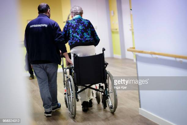 A physiotherapist helps an elderly woman to use a rollator on April 27 2018 in Berlin Germany