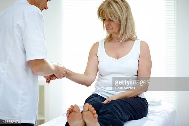 Physiotherapist massaging a hand of senior patient