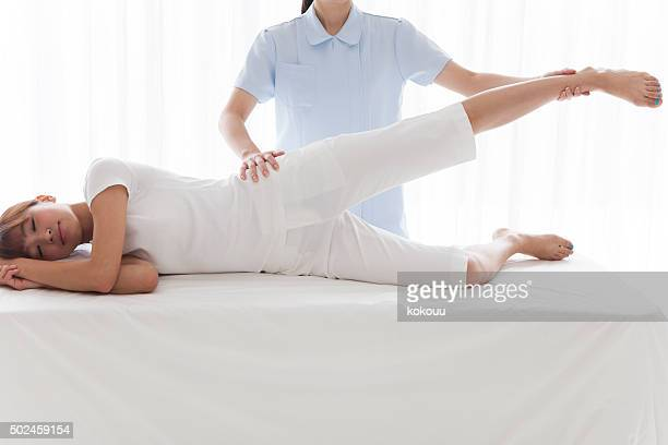 Physiotherapist massaging leg of young woman at spa