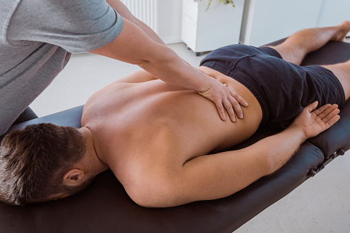 Physiotherapist massaging the back of the man 1125856047