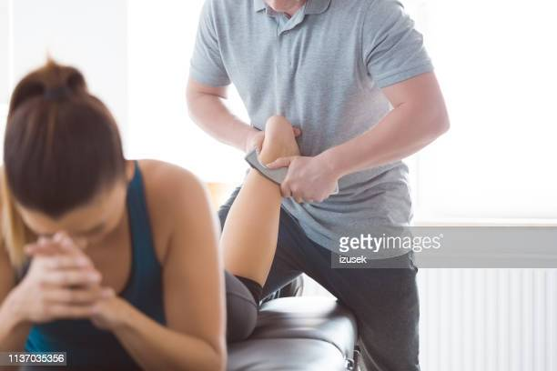 physiotherapist massaging woman's leg using tools - achilles tendon stock pictures, royalty-free photos & images