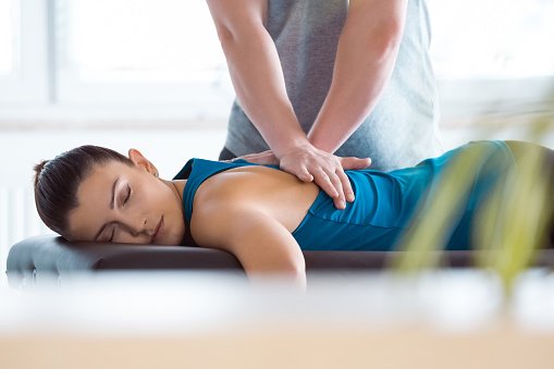Physiotherapist massaging young woman 1135761958