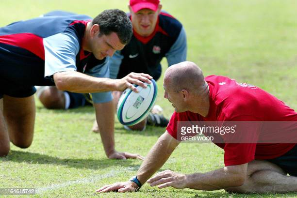 Physiotherapist Philip Pask with captain Martin Johnson and Neil Back takes England's World Cup rugby team through their warmups in the absence of...