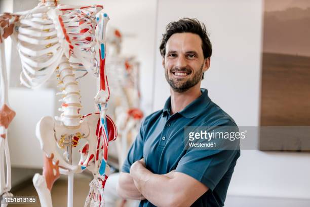 physiotherapist standing by anatomical skeleton with arms crossed - physical therapist stock pictures, royalty-free photos & images
