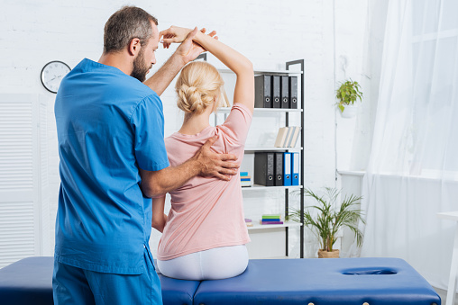 physiotherapist stretching patients arm on massage table in hospital 1036677088