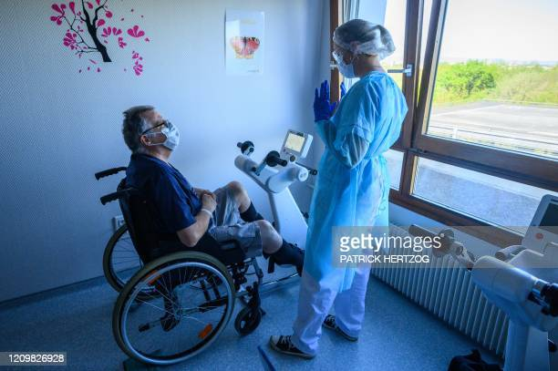 A physiotherapist takes care of a patient in rehabilitation as he recovers from an infection with the novel coronavirus COVID19 at a hospital in...