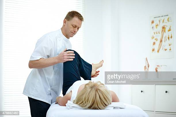 Physiotherapist treating knee of a female patient