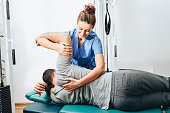 Physiotherapist treatment patient. She holding patient's hand, shoulder joint treatment
