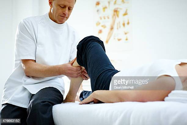 Physiotherapist working on woman's lower leg