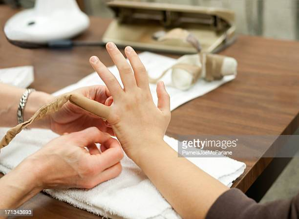 Physiotherapist Wrapping Patient's Finger to Control Swelling