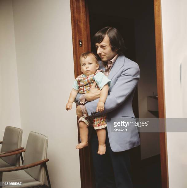 Pianist and conductor André Previn with one of his twin sons at London Airport, England, June 1971.