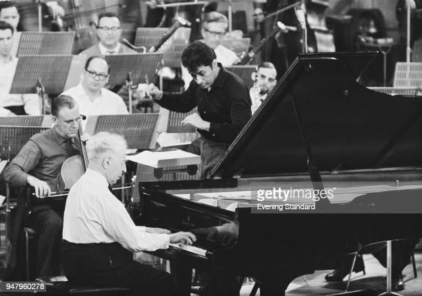 Pianist Arthur Rubenstein rehearsing with the Israel Philharmonic Orchestra conducted by Zubin Mehta for gala performance at Royal Festival Hall...