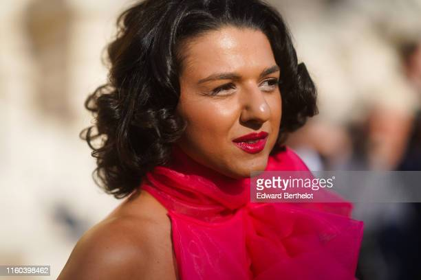 Pianist Khatia Buniatishvili wears a moire red halter top with a large bow collar outside Armani during Paris Fashion Week Haute Couture Fall/Winter...
