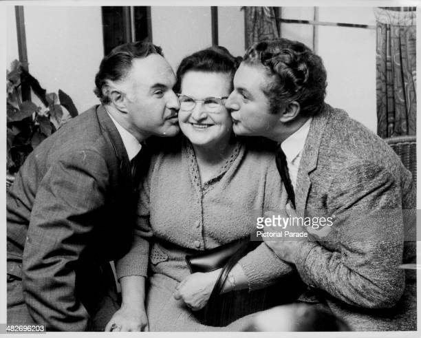 Pianist Liberace and his brother George kissing their mother on the cheeks Cherbourg France September 25th 1956