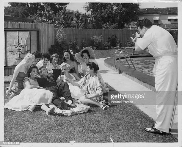 Pianist Liberace posing for a photograph by the pool surrounded by women including his wife sister and agents wife circa 19551960