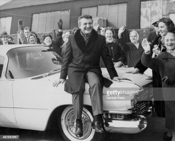 Pianist Liberace sitting on a Cadillac surrounded by fans London March 23rd 1960