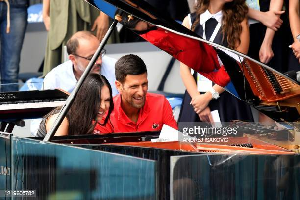 Pianist Lola Astanova performs as Serbia's Novak Djokovic looks on during a charity exhibition hosted by Novak Djokovic on June 12 2020 in Belgrade...