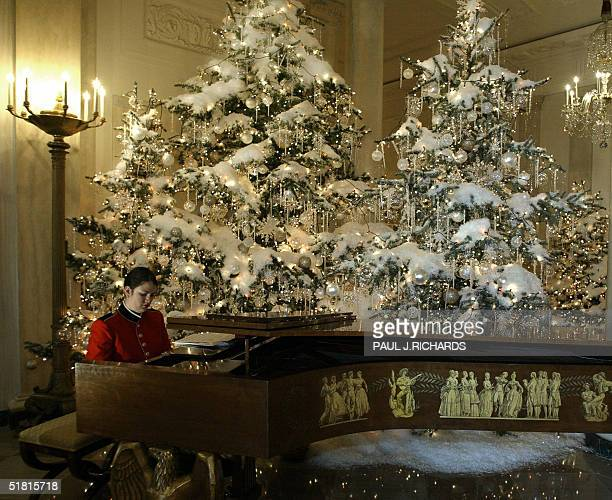 A pianist plays Christmas music on a Grand Piano inside the Cross Hall of the White House in Washington DC 02 December 2004 The entire White House...
