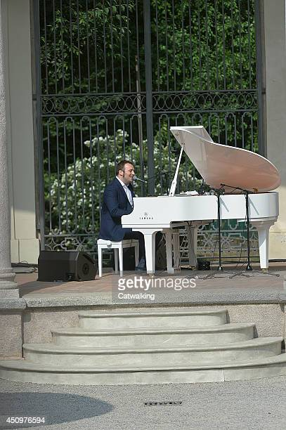 A pianist plays live on the runway at the Corneliani Spring Summer 2015 fashion show during Milan Menswear Fashion Week on June 21 2014 in Milan Italy
