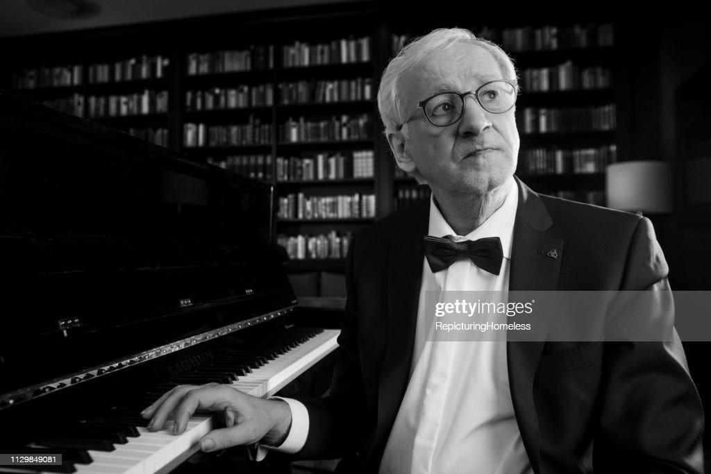 Ein Pianist sitzt vor dem Klavier und schaut mit einer Hand auf die Tasten. : Stock-Foto
