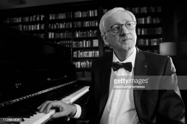 Ein Pianist sitzt vor dem Klavier und schaut mit einer Hand auf die Tasten.