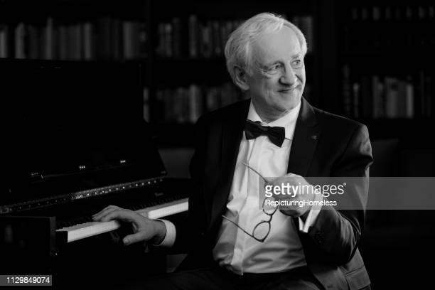 Ein Pianist sitzt vor dem Klavier und schaut mit einem strahlenden Lächeln weg.