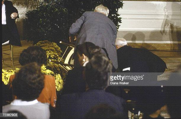 Pianist Vladimir Horowitz helping nancy Reagan to her feet after she fell off stage at WH