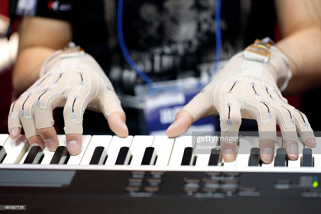 A pianist wears soft stretch gloves with Yamaha Corp.'s rubber-like stretchable strain sensor which measure the movement of the fingers as he plays piano at the Wearable Expo in Tokyo, Japan, on Thursday, Jan. 15, 2015. The world largest expo for wearable devices and technologies will be held through Jan. 16. Photographer: Kiyoshi Ota/Bloomberg via Getty Images