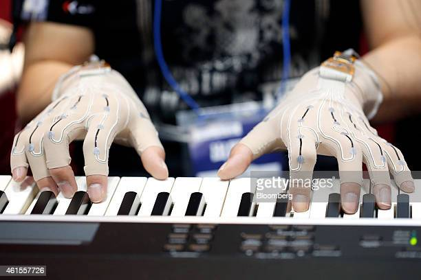 A pianist wears soft stretch gloves with Yamaha Corp's rubberlike stretchable strain sensor which measure the movement of the fingers as he plays...
