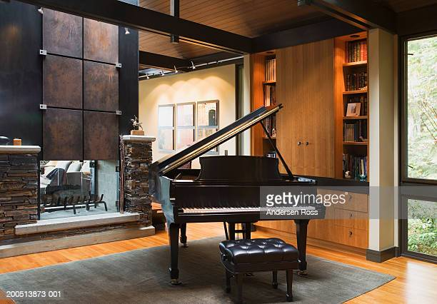 piano beside fireplace in living room - piano stock pictures, royalty-free photos & images