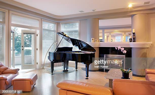 piano beside fireplace in living room - grand piano stock photos and pictures