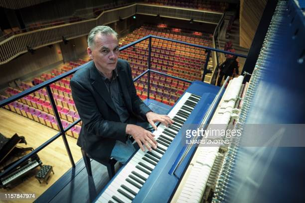 Piano constructor and builder David Klavins plays his new creation the M470i vertical concert grand piano with a height of 470 meters at the new...