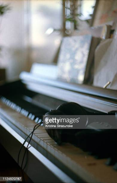 piano keyes and headphones - kristina strasunske stock photos and pictures