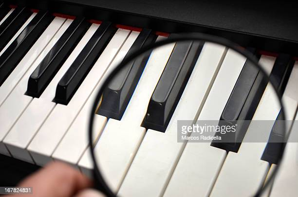 piano keys under magnifying glass - radicella stock pictures, royalty-free photos & images