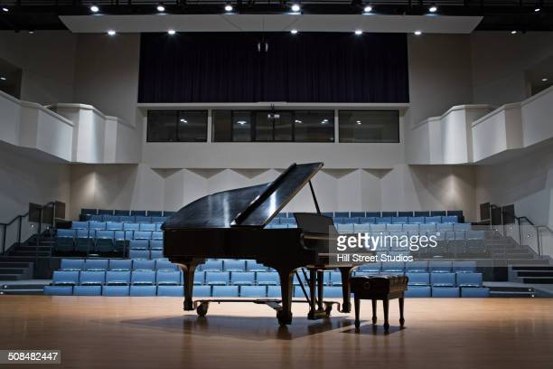 piano on stage in empty auditorium - grand piano stock photos and pictures