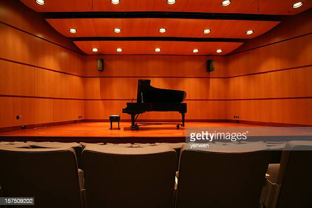 Piano sitting in the middle of the stage in an auditorium