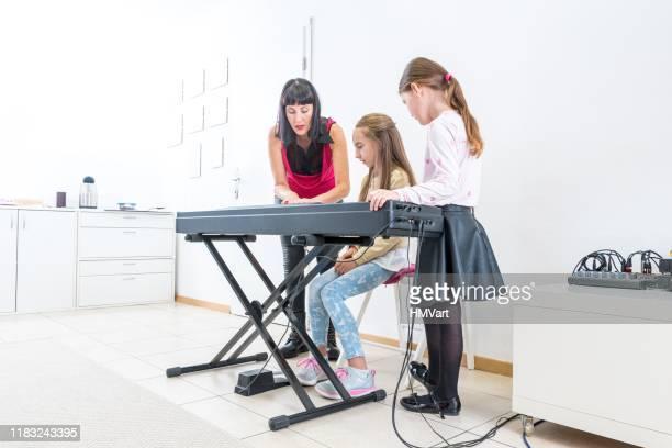 ピアノを弾くのが楽しいということを女子生徒に見せるピアノ教師 - キーボード奏者 ストックフォトと画像