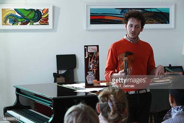 Piano tuner and technician Antoine Dubay holds a violin as he gives a workshop about the history of the piano and its mechanical parts near a...