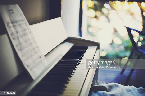 piano with balcony and bokeh in the background - sheet music stock photos and pictures