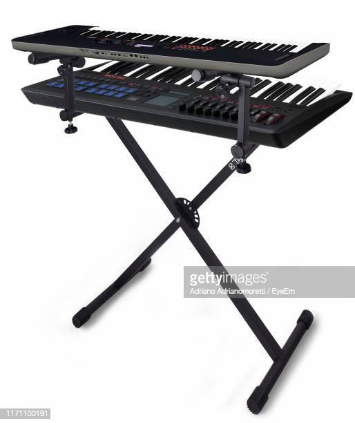pianos on stand against white background - piano key stock pictures, royalty-free photos & images