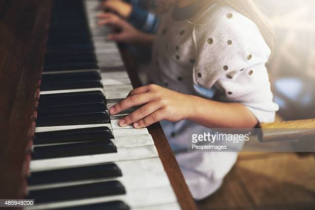 pianos unlock the keys to childhood talent - keyboard player stock photos and pictures
